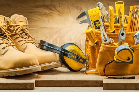 Photo for Boots earphones and toolbelt with construction tools - Royalty Free Image
