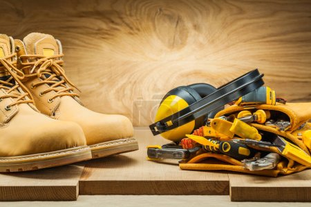 Photo for Boots and earphones on tool belt with construction tools - Royalty Free Image