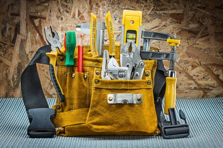 Photo for Leather toolbelt with many construction tools on plywood background - Royalty Free Image
