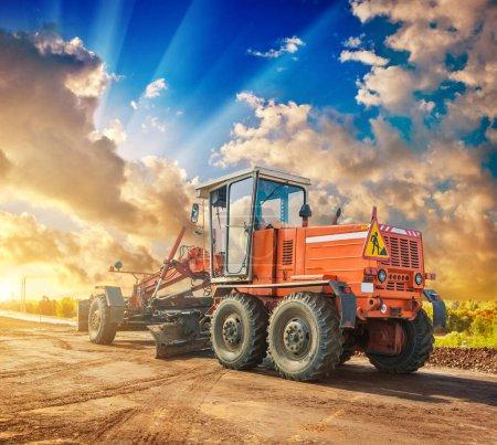 Photo pour Tracteur de construction vintage sur roues debout bord de la route belle vue coucher de soleil - image libre de droit