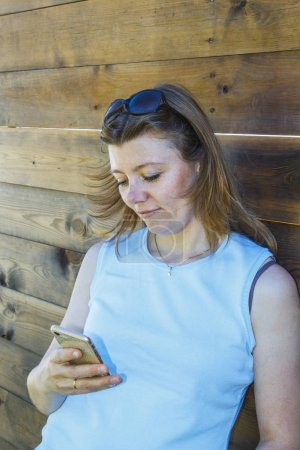 Photo for Beautiful girl in blue shirt using smart phone near wooden wall outdoors - Royalty Free Image