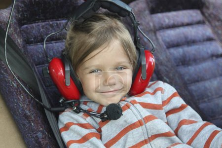 cute baby girl in headphones sitting in the cockpit of a small twin aircraft