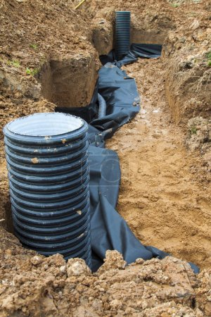 laying of drainage pipes and inspection well for removal of water from a site under construction of the house
