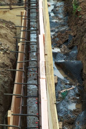 view of the construction site with wooden formwork, insulation and metal rods connected by wire. Preparation for Foundation pouring