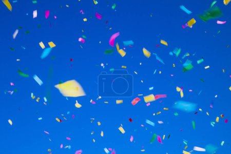 Photo for Multicolored confetti on clear blue sky background. Concept of holiday backdrop - Royalty Free Image