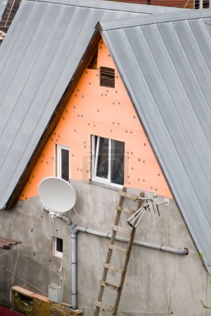 Foto de Fachada de la casa con placas de aislamiento bajo el yeso caído - Imagen libre de derechos