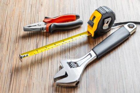 Photo pour Pinces réglables, clé et ruban à mesurer sur fond de table en bois - image libre de droit