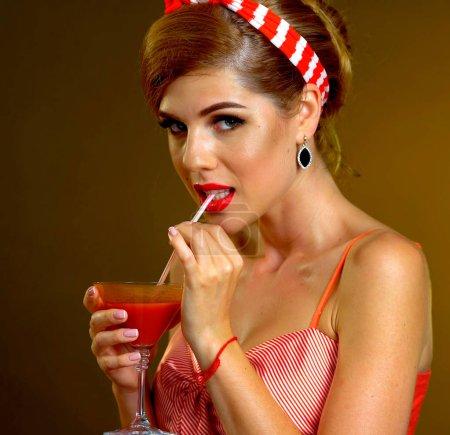 Photo pour Femme rétro avec disque vinyle de musique. Pin up girl boire cocktail de martini. Fille pin-up style rétro portant une robe rouge sur fond sombre. Superbe style de robe. Sexy fille dans le bar . - image libre de droit