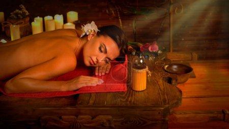 Photo pour Massage de femme dans le salon de spa. Fille sur fond de bougies dans la salle de thérapie. Intérieur luxueux dans le salon de thérapie orientale. Rayons de soleil fusées éclairantes pour les femmes se détendre après le sport. Lumière du matin de droite . - image libre de droit