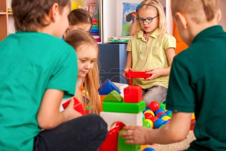 Photo for Children building blocks in kindergarten. Group kids playing toy on floor. Top view of interior preschool. Mat is big construction site building tower of cubes. Tournament of childrens creativity. - Royalty Free Image