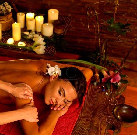 Aromatherapy massage of woman in spa salon.