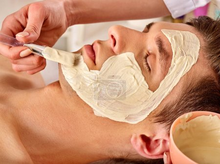 Mud facial mask of man in spa salon. Deep cleansing massage with clay face. Boy in therapy room lying . Anti-aging cosmetic mask.
