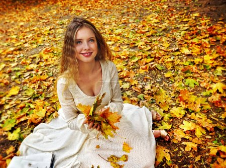 Autumn fashion dress woman sitting fall leaves city park outdoor.
