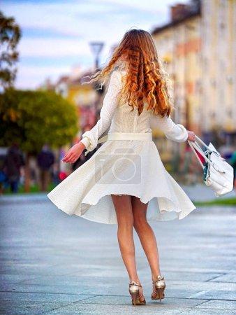 Foto de Mujer de moda en primavera otoño vestido en calle de la ciudad. Vista femenino estilo de modelo femenino moda chica con hilado de pelo de onda larga acampanada falda exterior posterior. Edificio y adoquines pavimento. - Imagen libre de derechos