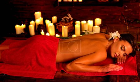 Photo for Massage of woman in spa salon. Girl on candles background in massage spa salon. Orchid in her hair. Luxary interior in oriental therapy salon. Spot light on dark background. - Royalty Free Image