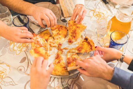 Friends eating pizza together, top view of the plate with hands grabbing pieces. Margherita, Italian pizza, shared by best friends at restaurant. Food and lifestyle concepts.
