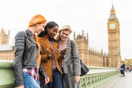 Foto de Grupo multirracial de chicas en Londres buscando a teléfono móvil con Big Ben de fondo. Tres mujeres en Londres que se divierten juntos. Conceptos de viajes y amistad - Imagen libre de derechos