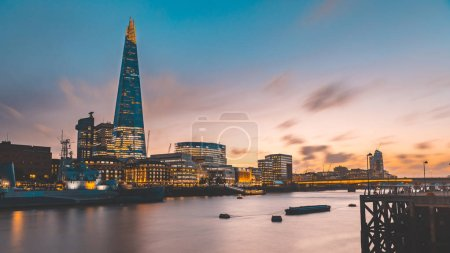 London skyline and Thames view at sunset with modern tall buildings and skyscrapers. Long exposure image with blurred clouds in the sky and water in the river. Architecture and travel concepts