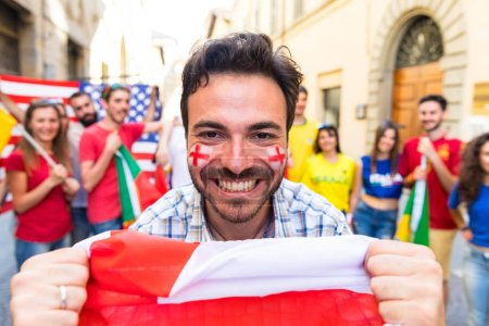 Happy England fan supporter at international match celebrating victory. Fans from other countries enjoying sport together. Sport, respect and achievement concepts
