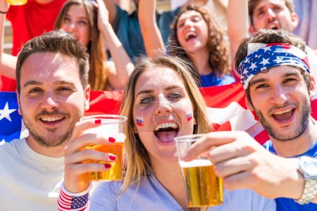 4th of July celebrations, Americans cheering with beers and USA flags. Big group of people, friends, chanting and cheering on National Holiday of Independence Day in the United States of America