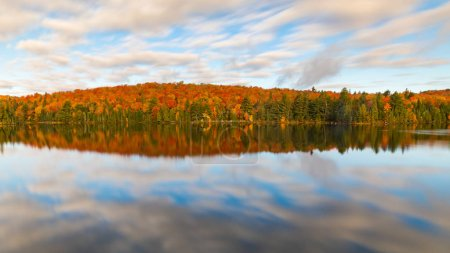 Colorful autumn trees reflections on the lake. Long exposure image with blurred clouds and silk water in Algonquin Park, Ontario, Canada. Relaxation, nature and autumn themes.