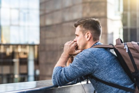 Photo for Thoughtful man alone in the city of London. Young caucasian man leaning against a railing over a bridge, sadness and solitude emotions. Job and life problems of a millennial - Royalty Free Image