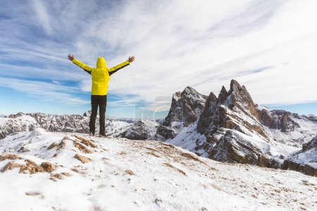 Successful man on top of snowy mountain. Happy hiker wearing a yellow jacket with raised arms looking at beautiful view on Italian Dolomites region. Adventure and travel concepts