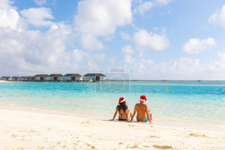 Photo for Couple with Christmas Santa hat relaxing at seaside. Holiday tropical destination postcard for holidays season with xmas hats. Man and woman sitting on the sand and looking away, travel and holidays concepts - Royalty Free Image