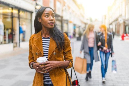 Photo for Black woman with two girls behind shopping and walking in London. Three girls, multiracial group, having fun in the city while shopping. Best friends sharing happiness, lifestyle and friendship concepts - Royalty Free Image