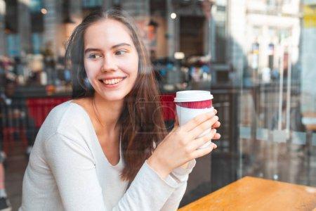 Photo pour Jeune femme dans un café profitant d'un café - Belle brune assise derrière une fenêtre dans un café bar à Londres, regardant loin de la caméra, bus rouge dans la réflexion - Style de vie et concepts de boissons alimentaires - image libre de droit
