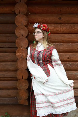 Photo for Teen in traditional Belarusian clothes on background of log cabin - Royalty Free Image