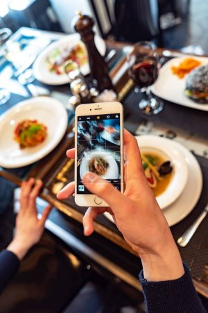Food: person taking mobile photo of soup