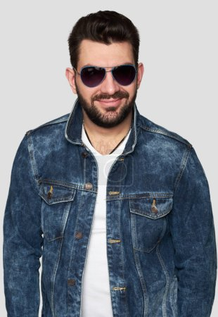 Photo for Handsome smug bearded man wearing sunglasses and trendy denim jacket. Isolated on gray background - Royalty Free Image