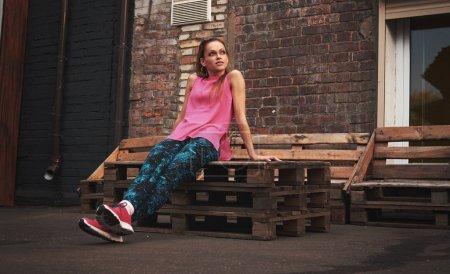 Photo pour Fitness sport femme en vêtements de mode dans les rues de la ville. Portrait de belle fille portant des chaussures de sport en plein air. - image libre de droit