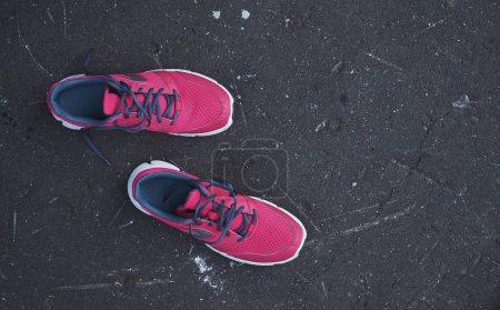 Photo pour Chaussures baskets roses sur une route asphaltée vue du dessus - image libre de droit