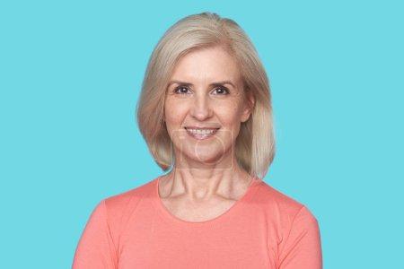 Photo pour Vieille belle femme blonde avec le sourire de dent isolé sur fond bleu - image libre de droit