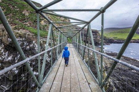 Photo for Kid walk on bridge in mykines, faroe islands - Royalty Free Image