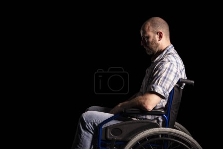 Photo for Portrait of caucasian man sitting in a wheelchair, sad and thoughtful expression. Black background. Concept of patient and physical disability. - Royalty Free Image