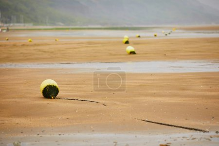 Buoys on beach of Villers-sur-Mer in Lower Normandy, France on a foggy day at low tide