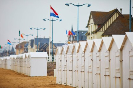Cabanas on beach of Villers-sur-Mer in Lower Normandy, France on a foggy day at low tide