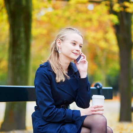 Beautiful young woman drinking coffee and speaking on the phone in the Luxembourg garden of Paris on a fall day