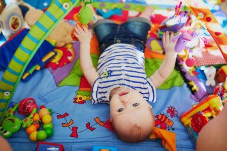 Foto de Niña con muchos juguetes coloridos. Niña tendida en una alfombra de juegos. Niño en la guardería . - Imagen libre de derechos