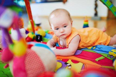 Foto de Niña con muchos juguetes coloridos. Niña mintiendo alfombra de juegos. Niño en la guardería . - Imagen libre de derechos