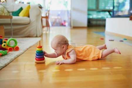 Foto de Niña jugando con apilar anillos de juguete. Niño tendido en el suelo con juguetes. Niño en la guardería . - Imagen libre de derechos