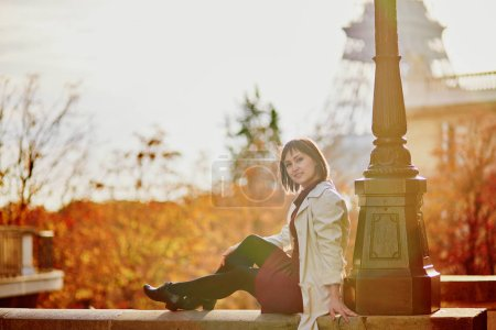 Beautiful young woman in Paris near the Eiffel tower on a bright fall day. Tourism and vacation in France at autumn season
