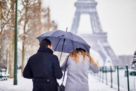 Photo pour Couple de touristes marchant à Paris sous parapluie une journée avec de la neige épaisse. Conditions météo inhabituelles à Paris - image libre de droit