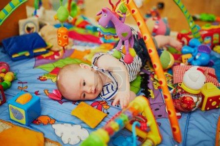 Foto de Niña con muchos juguetes coloridos. Niño pequeño acostado en la alfombra. Infantil niños en guardería. - Imagen libre de derechos
