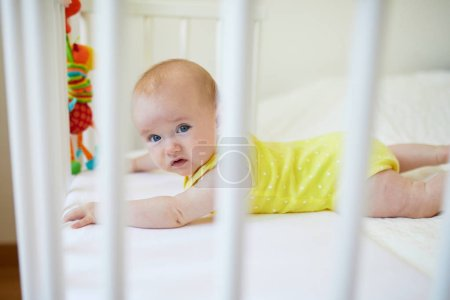 Adorable baby girl lying in co-sleeper crib attached to parents' bed. Little child not wanting day nap in cot. Infant kid in sunny nursery