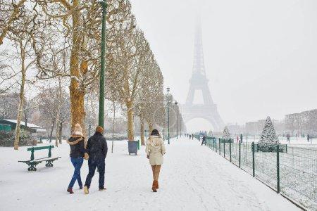 Photo pour Vue panoramique sur la tour Eiffel lors d'une journée enneigée. Les gens marchent par une journée enneigée à Paris. Conditions météo inhabituelles à Paris - image libre de droit