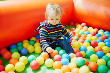 Photo for Little girl playing in ball pool. Toddler having fun with balls. Colorful toys for children. - Royalty Free Image